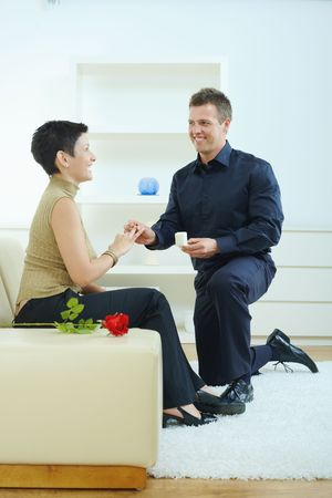 Man making a proposal on one knee, giving engagement ring to her fiencee. photo