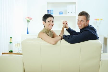 Happy young couple sitting together on couch at home, holding hands, smiling at each other. photo