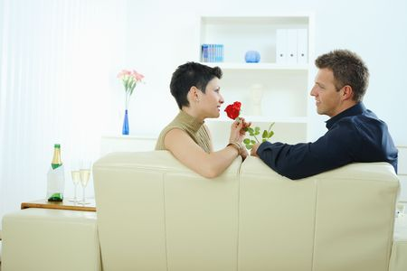 Romantic man giving red rose to woman at home, smiling. photo