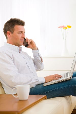 house call: Casual businessman working at home sitting on couch, using laptop computer, talking on mobile phone. Stock Photo