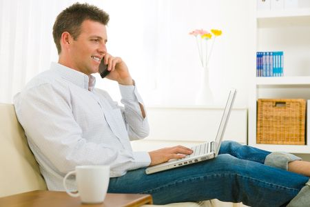 Casual businessman working at home sitting on couch, using laptop computer, talking on mobile phone. Stock Photo - 6463478