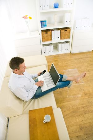 Casual businessman working at home sitting on couch, using laptop computer and mobile phone. High-angle shot. Stock Photo - 6463508