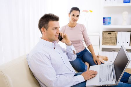 Young couple using laptop computer at home, sitting on couch. Man talkin on mobile phone. Selective focus on man. Stock Photo - 6463512
