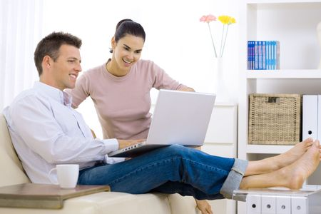 Happy couple browsing internet at home, using laptop computer, sitting on couch, smiling. photo