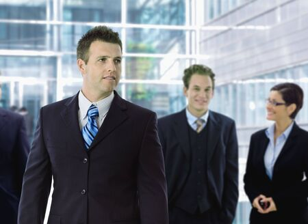 officetower: Young businessman standing in front of other businesspeople, out of office building.