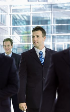 officetower: Young businessman standing among other businesspeople, in front of office building.