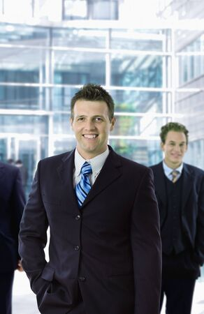 officetower: Happy businessman standing in front of office building, smiling. Stock Photo