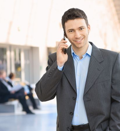 using mobile phone: Portrait of happy businessman talking on mobile in office hallway.