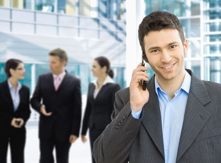 calling on phone: Portrait of happy businessman talking on mobile in office lounge. Stock Photo
