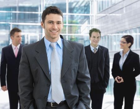 jovenes empresarios: Retrato de hombre de negocios feliz en pie en la sonrisa de sal�n de oficina.