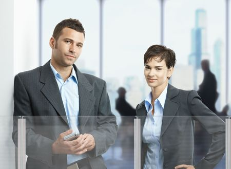 Two young businesspeople standing in corporate office lobby, looking at camera, smiling. photo