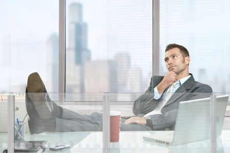 relaxed business man: Relaxed businessman sitting at desk in corporate office, thinking.