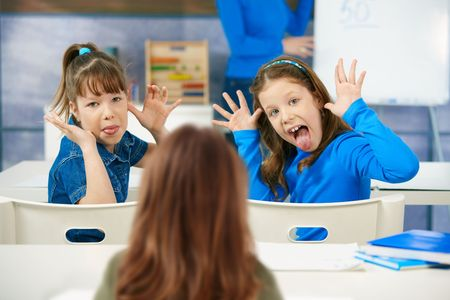 disrespect: Elementary age schoolgirls pulling faces to girl sitting behind, teacher at blackboard in background.
