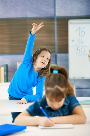 Schoolgirl in focus standing up in back row of class raising hand to answer question. photo