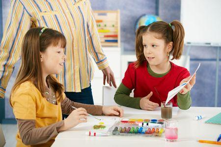 bambini seduti: Bambini in et� elementare seduti intorno scrivania godendo pittura con colori a lezione d'arte in aula della scuola primaria.