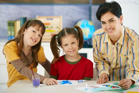 Portrait of elementary age children and teacher in art class in primary school classroom. Looking at camera, smiling. photo