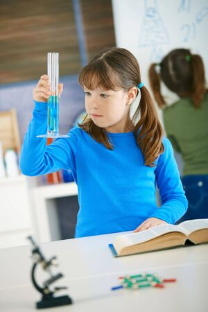Elementary age school girl looking at test tube in science class at primary school. Stock Photo - 6463682