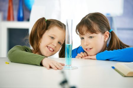 Elementary age school girls looking at test tube in chemistry class at primary school. photo