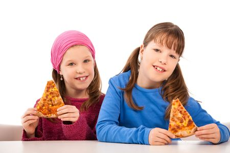 Girls smiling at table eating pizza slices. photo