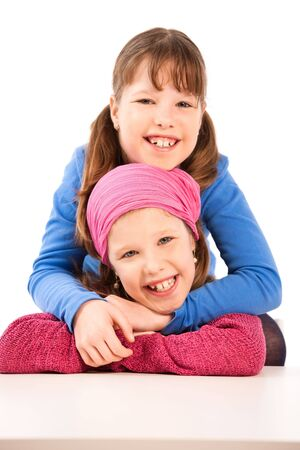 Portrait of happy elementary age schoolgirls hugging, looking at camera. photo