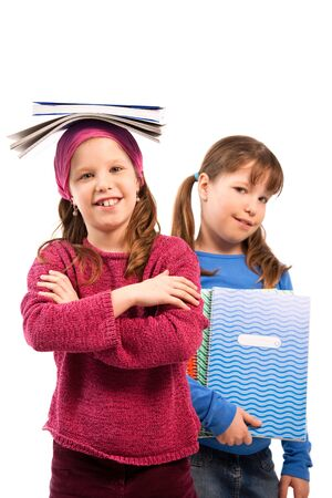Schoolgirls posing with exercise books, girl balancing books on top of head, other holding in arm. photo
