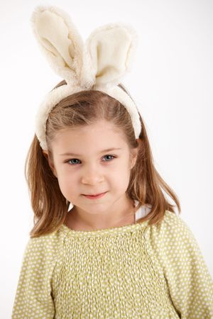 Portrait of smiling little girl wearing with rabbit ears for Easter, isolated on white backgorund. photo