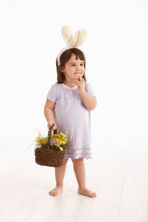 Little two years old girl wearing Easter bunny ears, isolated on white background. photo