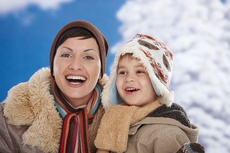 Portrait of happy mother and child  together in snow on a cold winter day laughing, smiling. photo