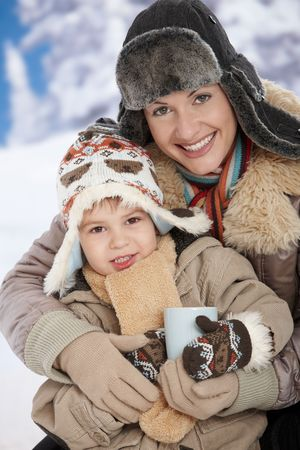Portrait of happy mother and child holding cup of hot tea in snow on a cold winter day laughing, smiling. Stock Photo - 6464866