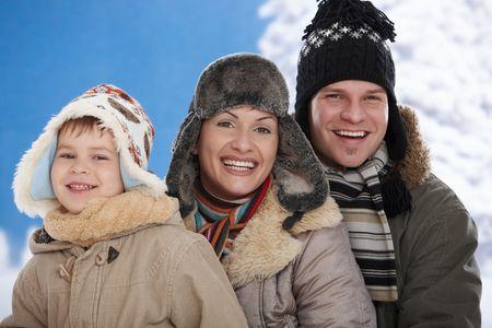 family one: Ritratto di famiglia felice insieme all'aperto nella neve in una fredda giornata d'inverno, ridendo, sorridendo.