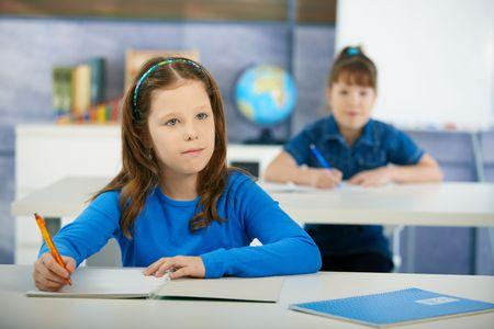 elementary age girls: Schoolgirls sitting at desk in primary school classroom. Elementary age children. Stock Photo