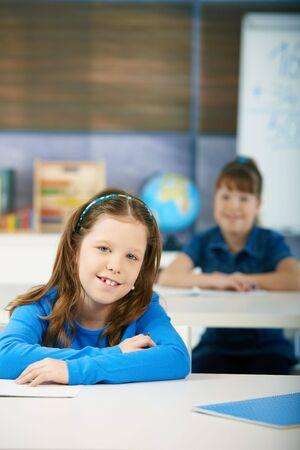 Happy schoolgirls sitting at desk in primary school classroom. Elementary age children. Stock Photo - 6463833