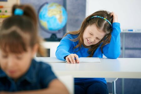 Schoolgirl thinking in primary school classroom. Elementary age children. Stock Photo - 6463828