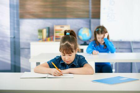bambini seduti: Bambini alla scrivania in Aula di scuola primaria, apprendimento matematica. Bambini in et� scolare.  Archivio Fotografico