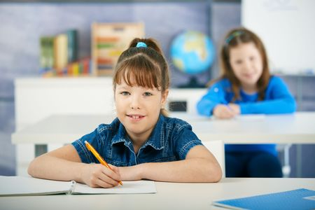 room mate: Schoolgirls sitting at desk in primary school classroom. Elementary age children. Stock Photo