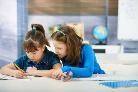 elementary age: Children sitting at desk working together in primary school classroom.  Elementary age children.
