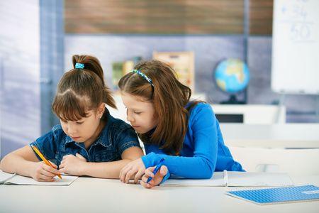 schoolchild: Children sitting at desk working together in primary school classroom.  Elementary age children.