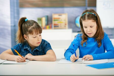 Children sitting at desk working together in primary school classroom.  Elementary age children. photo