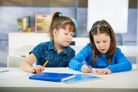 scholars: Children sitting at desk and learning together in primary school classroom. Elementary age children.