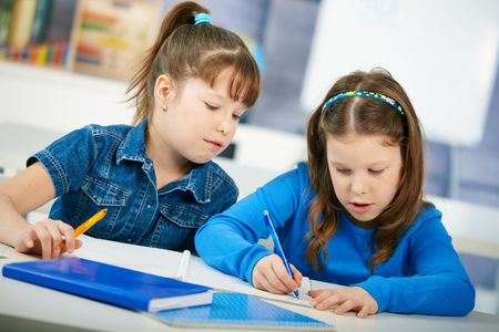 kids writing: Schoolgirls learning together in primary school classroom. Elementary age children.