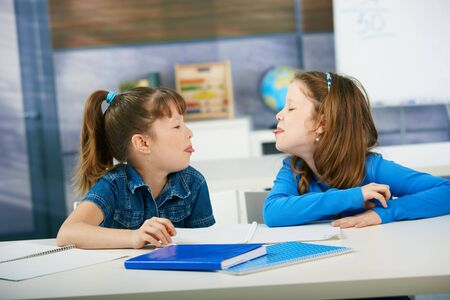cooperating: Children sticking out tongue to each other in primary school classroom. Elementary age children.