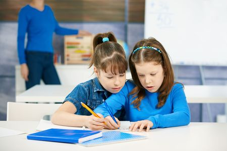 cooperating: Children learning together in primary school classroom. Schoolgirls in elementary age.