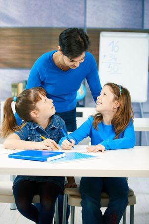Niños en edad de primaria escuchando a la maestra en el aula de la escuela. Sonriente, feliz. Foto de archivo - 6463929