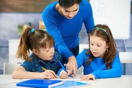cooperating: Elementary age children listening to female teacher in school classroom.