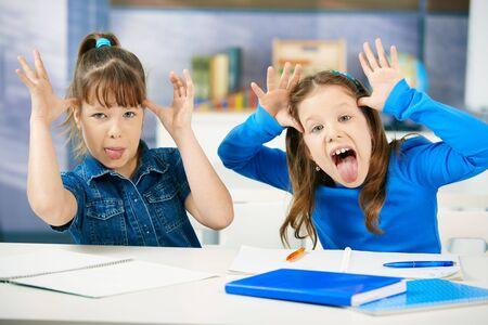 irrespeto: Niños que fuera la lengua en el aula de la escuela primaria. Colegialas en edad primaria. Foto de archivo