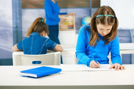 aside: Elementary age schoolgirls writing tests at class seated aside, teacher standing in the background. Stock Photo