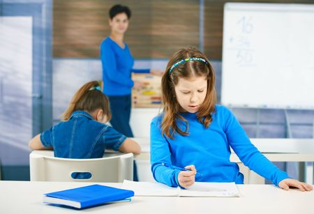 Schoolgirl thinking while filling out test at class, teacher standing in background. photo
