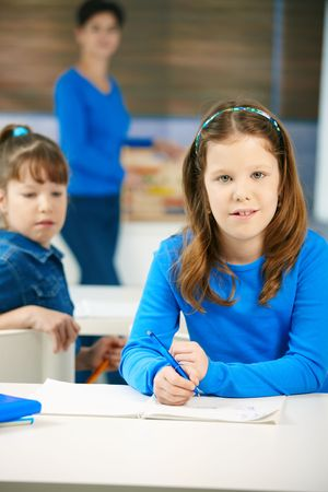 Portrait of elementary age schoolgirl sitting at class looking at camera, with other student and teacher in background. photo