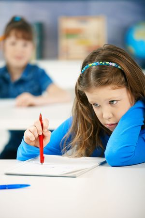 elementary age girls: Elementary age schoolgirls writing tests, focus on girl sitting in the front, holding pen thinking what to write.