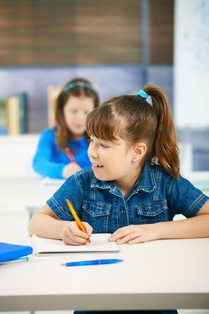 age test: Schoolgirl smiling looking aside while writing test in class, other student in background.